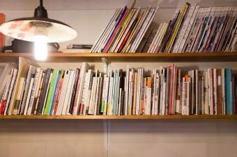 手作りの棚に仕事関係の本を並べる。照明のやさしい灯りが和める雰囲気。