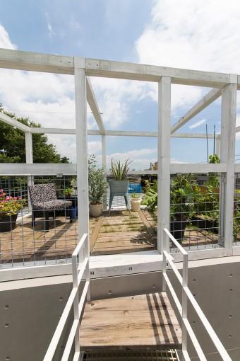 理恵子さん夫妻の住まいになっている3階のリビングから、ブリッジを渡って屋上のグリーンスペースに出ることができる。