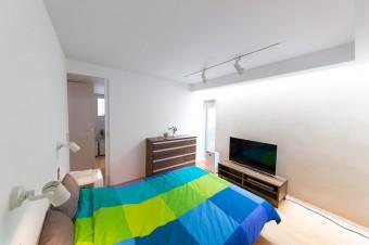 天井から、ガラス越しの自然光が柔らかく差し込むベッドルーム。壁の色も落ち着いたベージュカラーになっている。