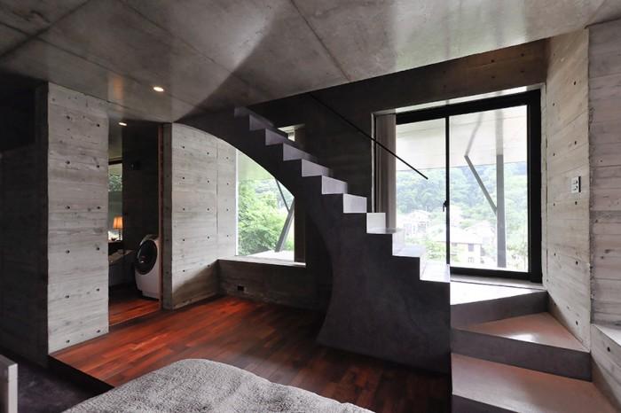 寝室部分から階段と左に浴室入口を見る。このスペースも開口は大きめだが張り出した部分が前面にあるため上階よりも光はやさしめ。軒先の深い伝統的な日本家屋の奥にある部屋のイメージという。時間により陰翳の状態が徐々に変化していく。