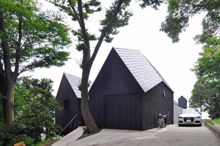 左がLDKスペースの納まる棟、右が手前に車庫、その奥にアトリエ、その階下に寝室などが収まる。