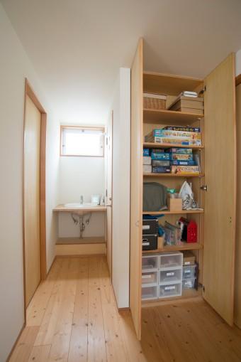 子供のおもちゃなどが整然と片付けられた2階の収納。洗面台の下は、あえて棚を設けなかった。