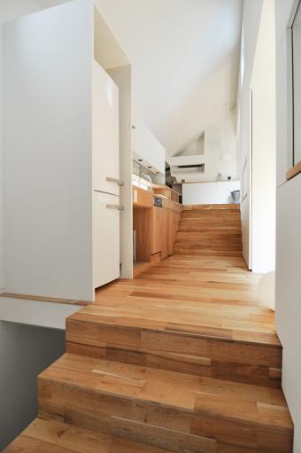 階段状に連なる空間の中で、キッチン前の空間は広めの踊り場にも見える。ここを右に折れると食事の間。