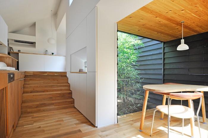 左のキッチンスペースから隣の食事の間へは移動もスムーズ。天井高のある空間から移るとスケールを抑えた空間の親密さがなお一層引き立つ。