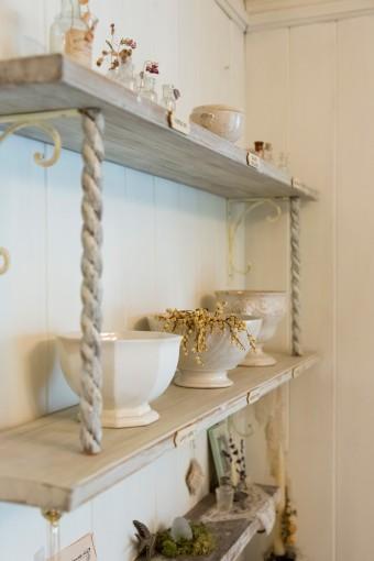 アンティークの器や小瓶など、大切なものを自作の棚にディスプレイ。壁面には板を貼った。