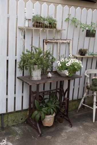 ツルバラなどが美しく咲く庭は、アンティーク風に作り替え手入れを楽しんでいる。古いミシン台を活用。