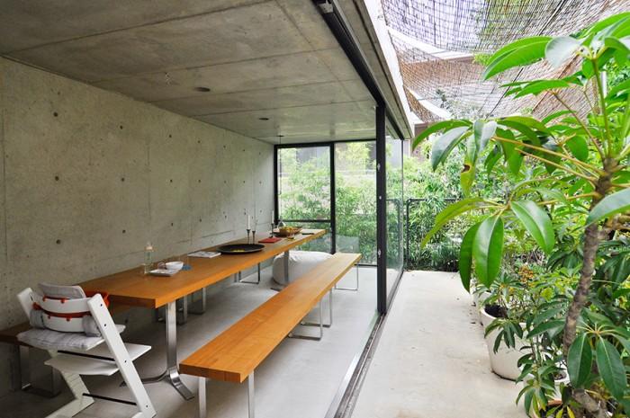 3階奥のダイニングペース。建物が建て込んだ場所ながら緑に囲まれて暮らす。ガラス窓を開けると外部と一体化。街の真ん中で実現した開放感のある住まいだ。