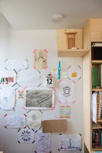アトリエの壁には子供の作品やアート作品などを貼る。後から造りつけた本棚の脇には神棚も設置。