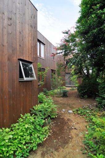 左から玄関棟、リビング棟、寝室棟。右側にサルスベリの木など緑が豊富な庭