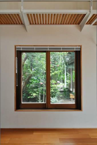 窓で切り取られた外の緑の景色が素晴らしい。湿気がこもらないようにという要望から壁は珪藻土に。