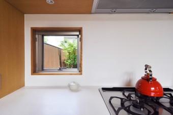 キッチンの小窓から敷地のいちばん奥にある緑を見る。