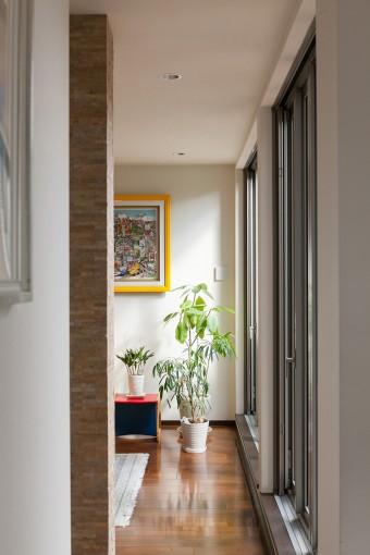 ダイニングから廊下越しにリビングを見る。壁のアートはチャールズ・ファジーノの作品。