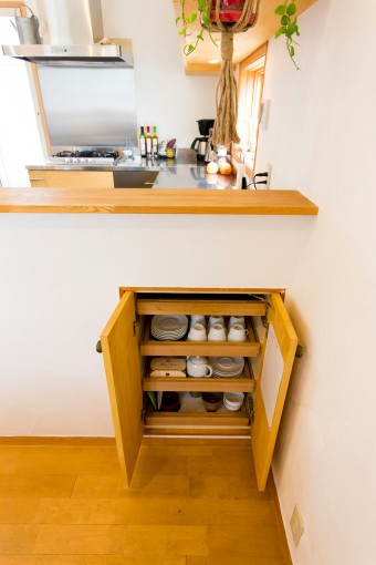 食器などを入れる小さな棚を、ダイニング側のカウンター下に設置。扉の右手はお手伝い記録シート。