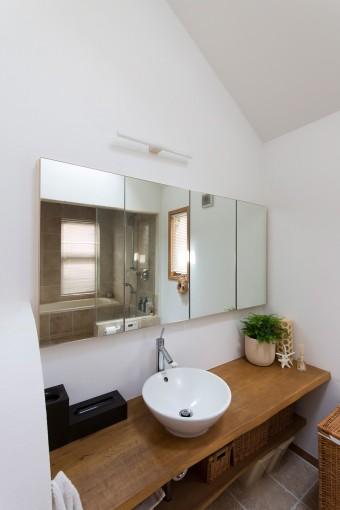 バスルームの洗面。天然素材を活かしたシンプルな造りが、ホテルのような雰囲気。