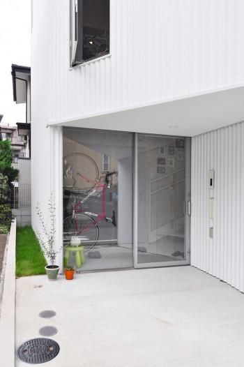 大きく開けた玄関が十分な光を1階に取り込む。隣地との間に芝生を植えたのは建築家のアイデアに呼応した奥さんの発案。