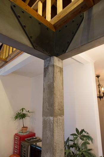 木の柱をコンクリートで巻いている。構造の補強金物に見えるパーツは、実は木の造作。