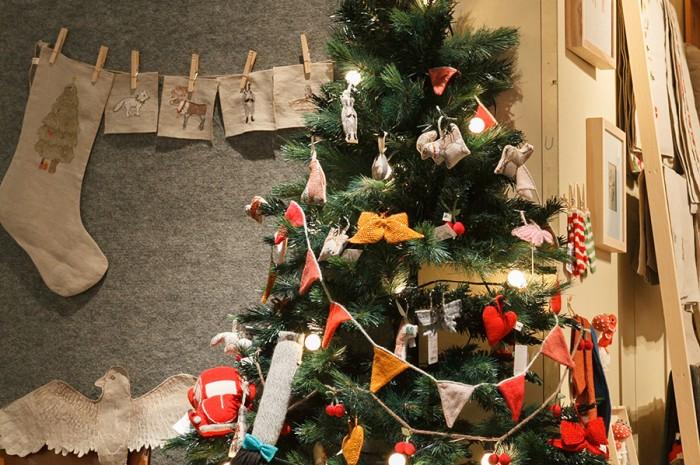 コーラル・アンド・タスクのリネンオーナメントと、ウフのニットガーランドで飾られたユニークで優しいクリスマスツリー。