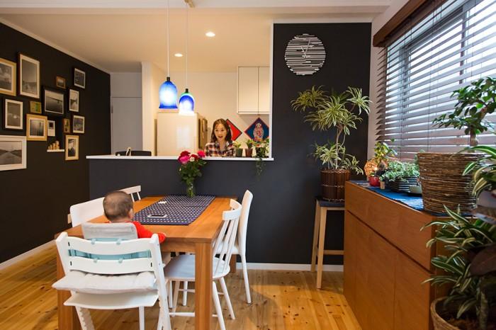 """壁紙のカラーが部屋全体の印象を引き締めている。家具は主にアクタスのもの。テーブルは""""REN""""、キャビネットは""""シャイン""""シリーズ。"""