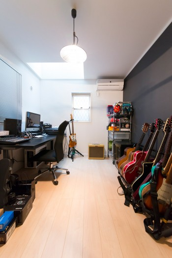 ギター、カメラなど夫の趣味の道具を揃えた1階のホビールーム。黒い壁紙がクール。