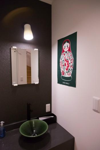洗面の流しは陶磁器製。お気に入りのマトリョーシカのポスターを飾る。