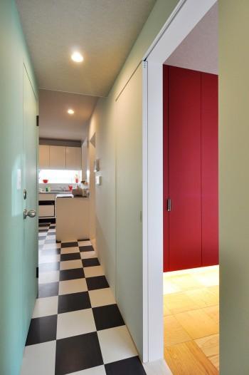 白と黒の市松模様が玄関脇の廊下からキッチンへと続く。グリーンの壁との組み合わせは奥さんが希望されたもの。