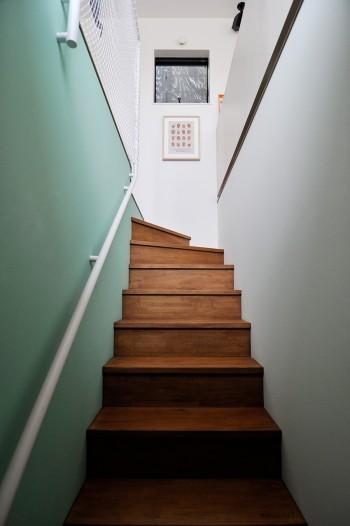 3階へと上る階段。濃いめの色合いが壁のグリーンとしっくりと合っている。