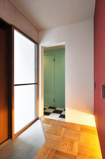 左の玄関から入ると正面にレッド系の色の塗られた壁が目に入る。左を向くとグリーンの壁と市松模様の床が見える。