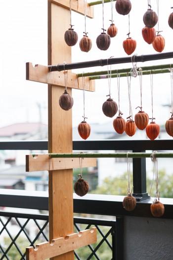 干し柿が好きという柴原さん、ベランダで渋柿を干していた。干し柿用の台も自作。