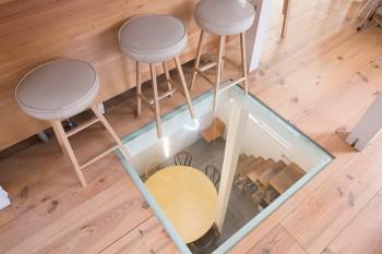 1階の打ち合わせスペースを見下ろせるガラス窓。床は無垢のパイン材を使用した。