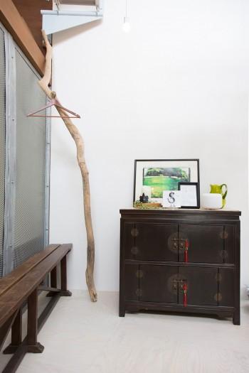李朝の家具の横には、海で拾ってきた流木がハンガーラックに。パンチングメタルの仕切りは、浴室の窓にもなっている。