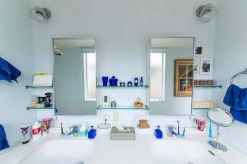 2つのシンクに合わせて、鏡などをシンメトリーに配置。小物もテーマカラーの青を選択。