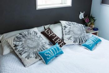 ベッドメイキングは毎日欠かさない。クッションにも青と黒を取り入れてコーディネート。