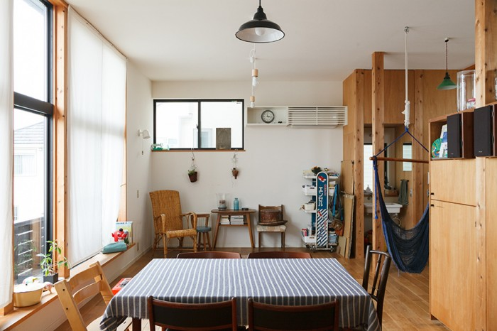 キッチンからリビングを見る。ひとつずつデザインの異なる椅子や家具が独特の味わいを醸し出す。南側の開口部にはベンチになるステップを設けている。