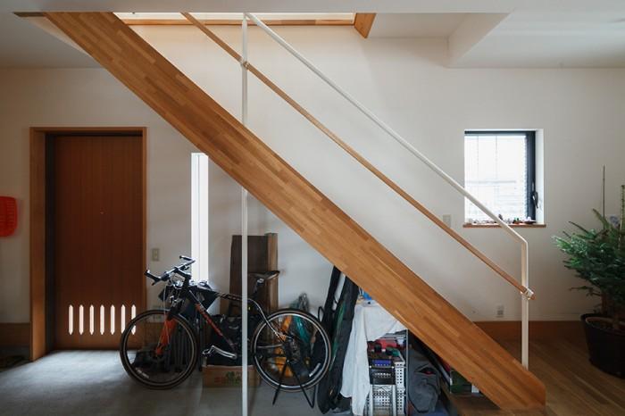 階段下のスペースにアウトドア関連のものを収納。左手の引戸が玄関ドア。