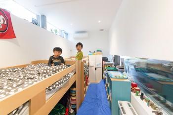 ACTUSの子どもベッドを縦に並べた翔雲くんと海琉くんの部屋。右側のガラスの向こう側はガレージになっている。