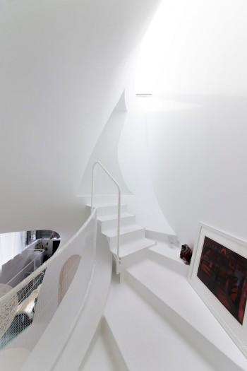 トップライトからの光が、曲線の白の壁に美しいニュアンスを与えている。