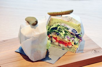 オススメのベジタリアンサンドウィッチ。ほうれん草を練り込んだブレッドにアボカド、トマト、キュウリ、季節の野菜がボリューミーにサンドされた一品。¥1,500