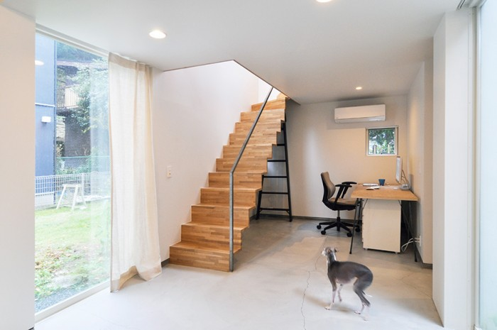 右側の棟の1階にある仕事場。ソファの置かれたスペースと1室空間のようにつくられていて広く、仕事をしながら犬の面倒も見られるのでいいという。手前はグレイハウンドのファニー。