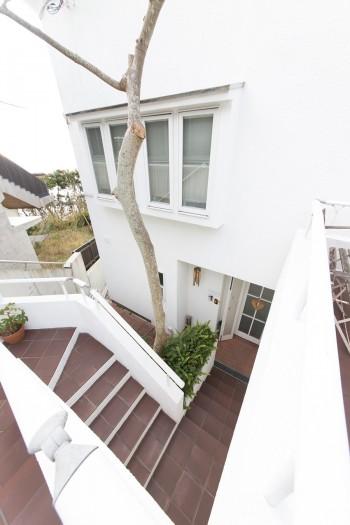 山の傾斜に沿って建つため、1階の玄関は階段を降りていったところにある。
