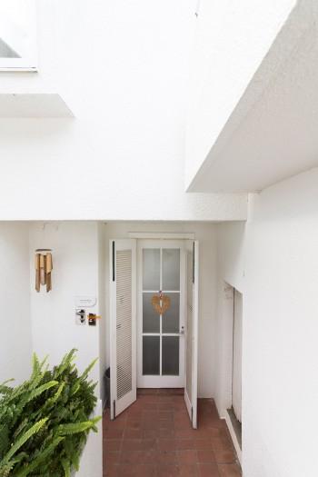 ルーバーの扉の向こうにもう1枚ドアが。潮風を感じる、リゾート物件のような造り。