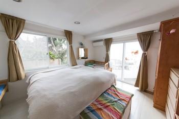 ベッドルームも海に面した贅沢な造り。庭の緑も心地よい。