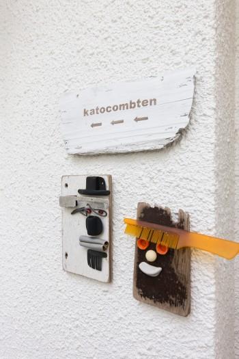 玄関にはkatocombten(コーム&工務!)の案内が。オブジェは海で拾ったもので作品を作る作家・シキヤンのもの。