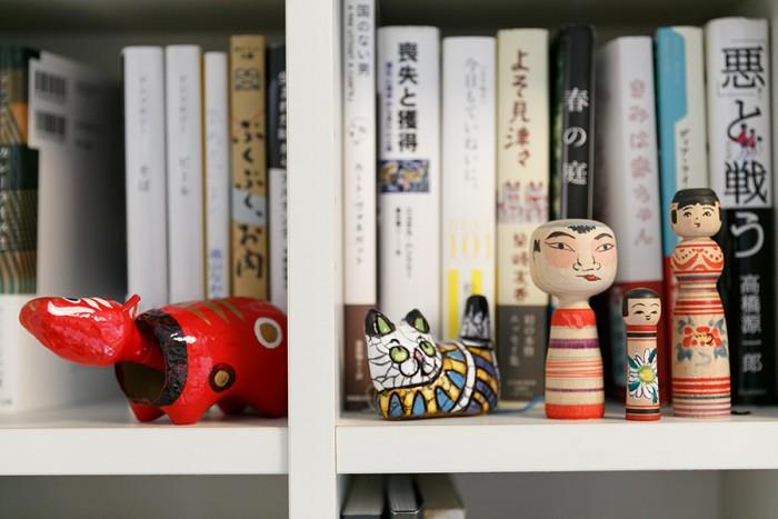 夫妻の蔵書が並ぶ本棚には伝統こけしや赤べこが。