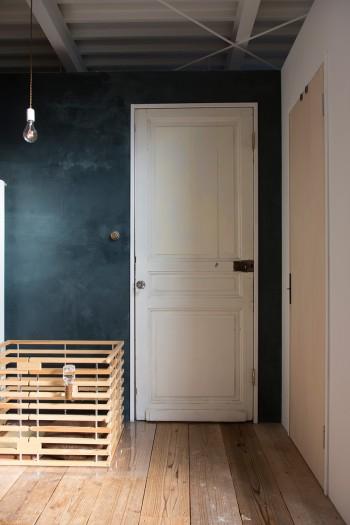 味わいのある壁色と、年代物のドア。天井部分は隙間を空け、部屋と部屋をボックス状に仕切ることで空間に広がりが感じられる。
