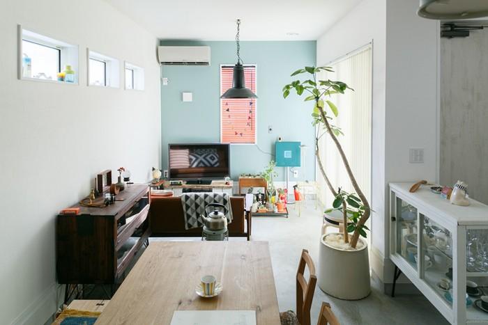 大きな掃き出し窓から明るい日差しが入る土間のリビングダイニング。奧の壁にはチョークで落書きが出来るチョーク塗料を塗った。色はクレイブルー。ブラインドのオレンジとのコントラストが鮮やか。