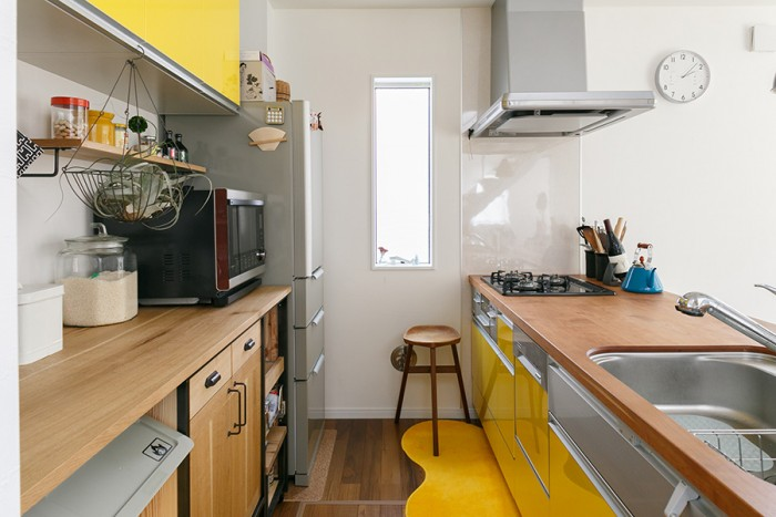 黄色を取り入れた明るい印象のキッチン。この家のカラーコーディネートの決定権は章子さんにあるそう(笑)。キッチンカウンタートップには章子さんが好きなアメリカンチェリーを用いた。