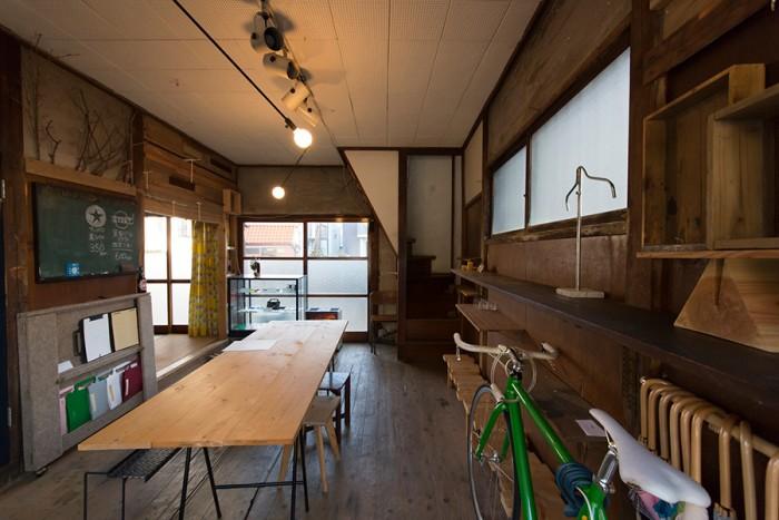 1階のギャラリー。解体時に出た廃材を使って、劣化した壁をアレンジ。中央のテーブルは用途に応じて簡単にバラすことができる。