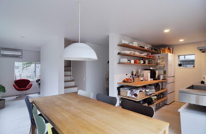 手前がダイニングで右がキッチン。左手奥はさらに右に小さなスペースがあり、子供たちのお気に入りのスペースという。キッチンの収納は見えやすさと使いやすさを考え、扉はつくらずオープンなつくりにしたという。