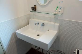 洗面所の壁はタイルと漆喰で構成。坪井さんがデザインしたガラスの棚受けなど、「Losango」の商品を使用。