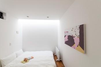 3階の寝室。収納もないシンプルな室内にトップライトの光が落ちる。壁の絵は水野健一郎さんの作品。